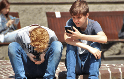Two boys staring at mobile phones
