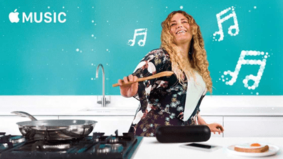 A lady dancing to Apple Music while she cooks